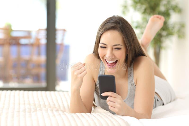 Upphetsad vinnare som hemma kontrollerar telefonen royaltyfri foto