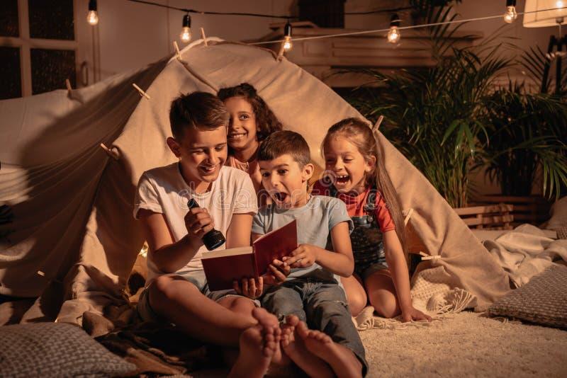 Upphetsade barn med hemmastadd ljusare läsebok royaltyfria bilder
