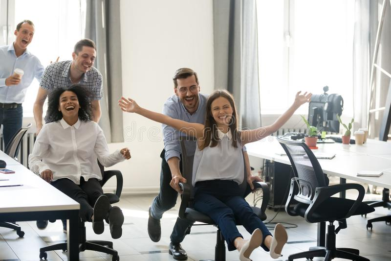 Upphetsade bekymmerslösa olika kontorsarbetare som har gyckel under arbete b royaltyfri bild