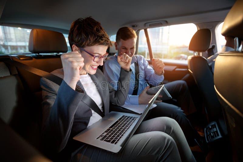 Upphetsade businesspeople som ser bärbara datorn i bil på tur arkivbild