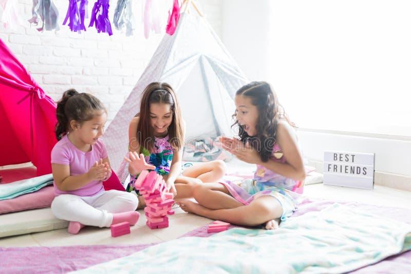 Upphetsade flickor som spelar med träkvarter under Pajamapartiet royaltyfri fotografi