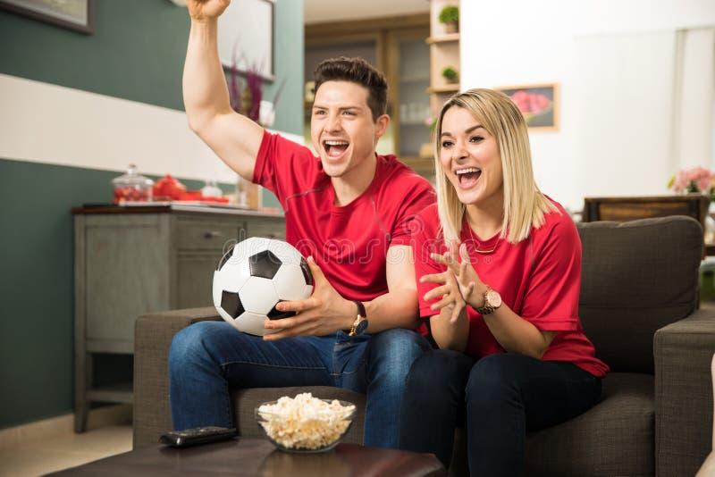 Upphetsade fotbollfans som håller ögonen på leken royaltyfria bilder