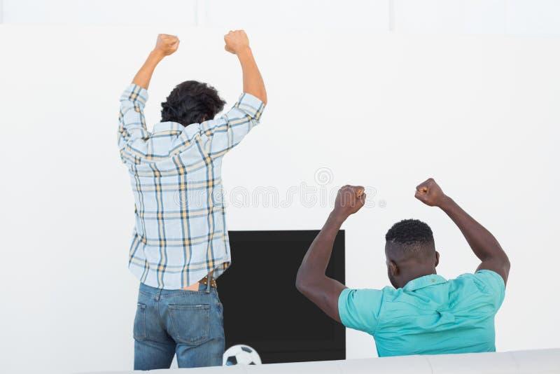Upphetsade fotbollfans som hurrar, medan hålla ögonen på tv royaltyfri fotografi