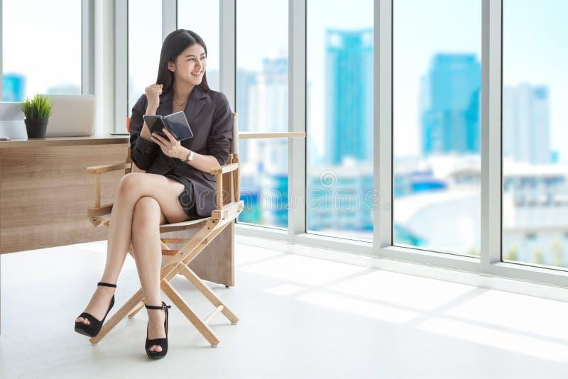 Upphetsade härliga asiatiska unga affärskvinnahälerigoda nyheter royaltyfria bilder