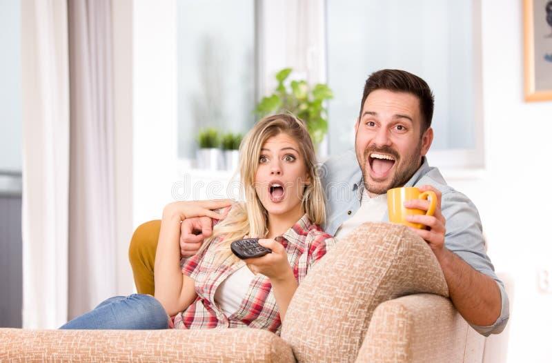 Upphetsade hållande ögonen på tv och känsla för par arkivfoto