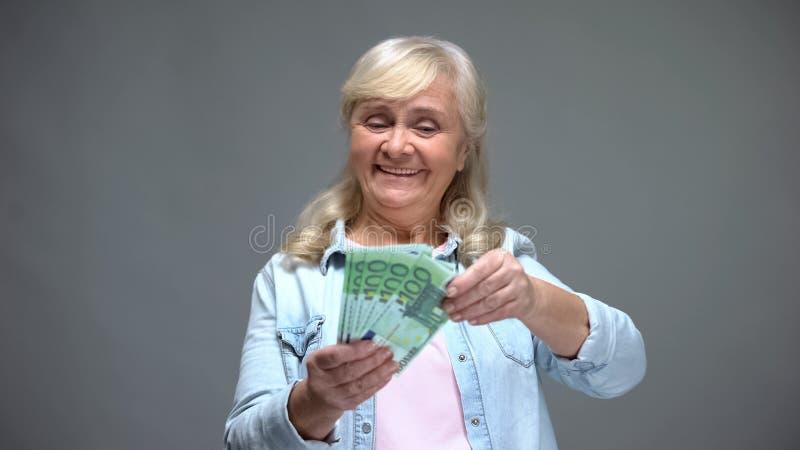 Upphetsade höga kvinnliga räknande eurosedlar som planerar köp, lånservice royaltyfri foto