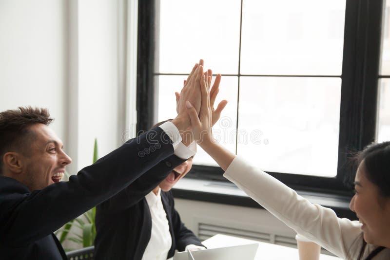 Upphetsade kollegor som ger nående mål för höjdpunkt fem arkivfoton