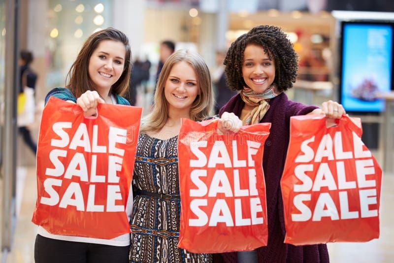 Upphetsade kvinnliga shoppare med Sale påsar i galleria royaltyfri bild