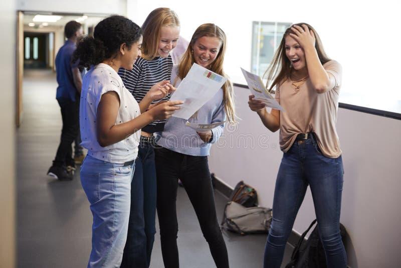 Upphetsade kvinnliga tonårs- högstadiumstudenter som firar examenresultat i skolakorridor royaltyfri fotografi