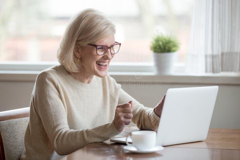 Upphetsade läs- goda nyheter för lycklig mogen affärskvinna som ser arkivfoto