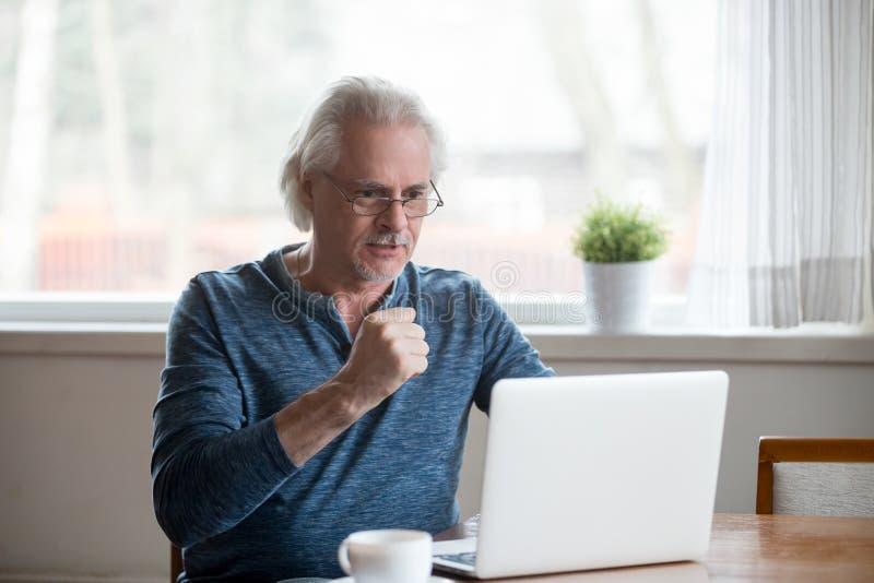 Upphetsade lyckliga läs- goda nyheter för hög man på bärbara datorn royaltyfria bilder