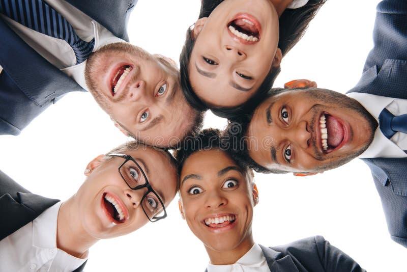 upphetsade multietniska businesspeople i formella kläder som ser kameran royaltyfria foton