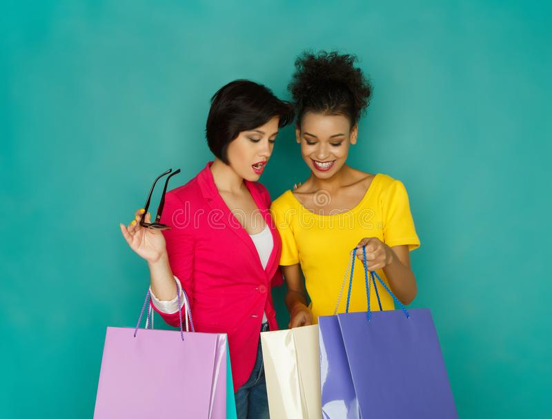 Upphetsade multietniska flickor med shoppingpåsar royaltyfri foto