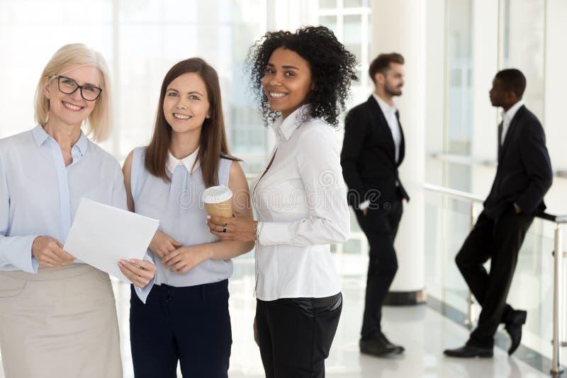 Upphetsade olika kvinnliga kollegor för stående som i regeringsställning ser kameran arkivbild