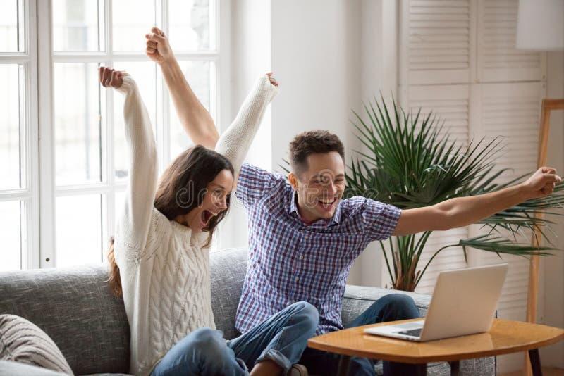Upphetsade par som lyfter händer som ser bärbara datorn som direktanslutet firar royaltyfri fotografi