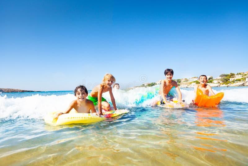 Upphetsade pojkar som rider vågorna på kroppbräden fotografering för bildbyråer