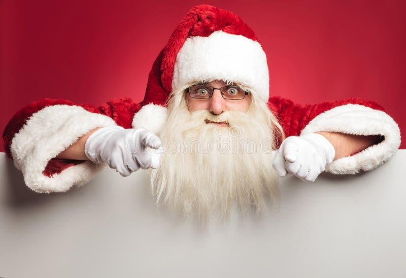 Upphetsade Santa Claus överst av affischtavlan som pekar hans fingrar royaltyfri foto