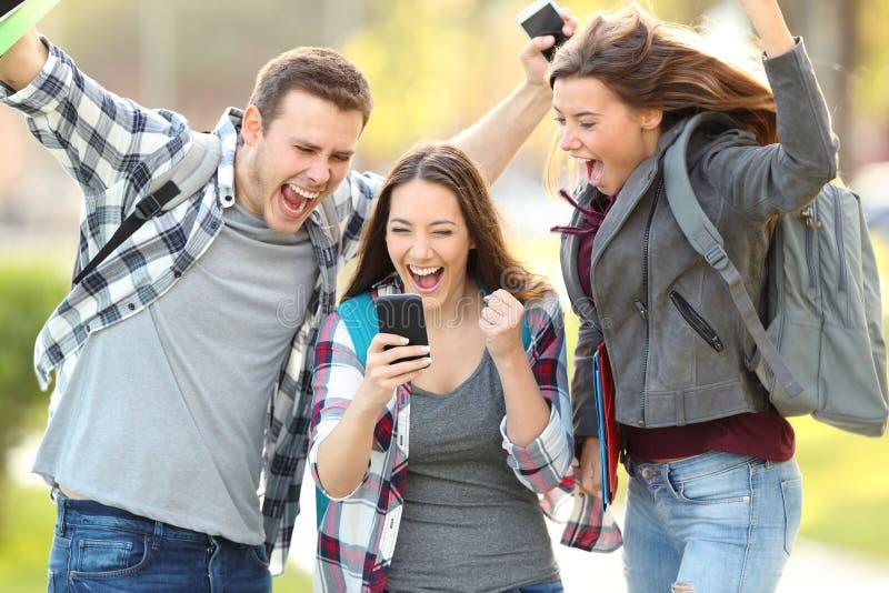 Upphetsade studenter som direktanslutet kontrollerar examenkvaliteter arkivbild