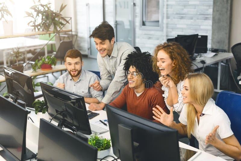 Upphetsade studenter som tillsammans läser goda nyheter på datorskärmen fotografering för bildbyråer