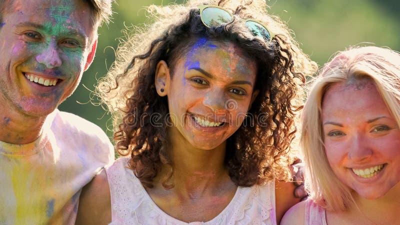 Upphetsade ungdomarmed framsidor som täckas i färger, vänner som ler för kamera royaltyfri bild