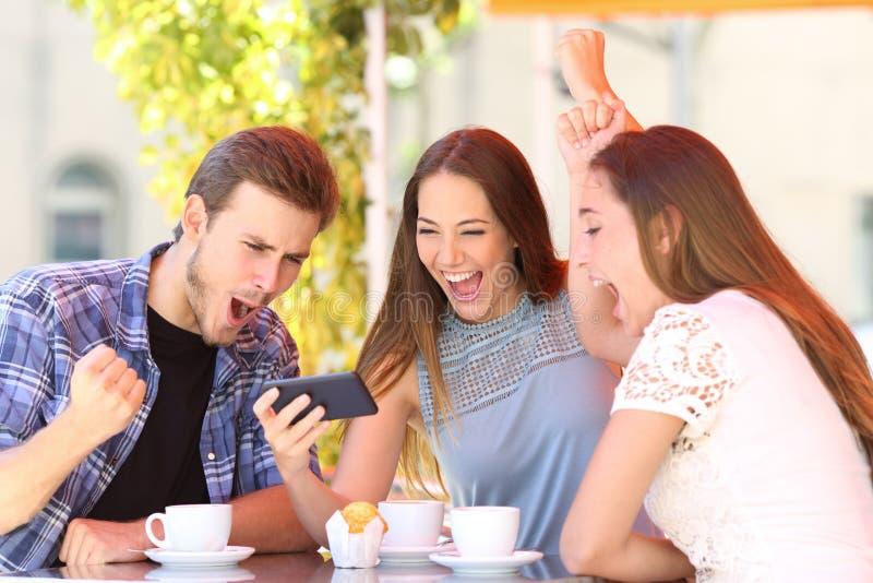 Upphetsade vänner som firar det hållande ögonen på telefoninnehållet för goda nyheter fotografering för bildbyråer
