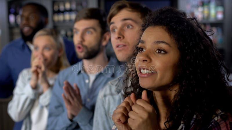 Upphetsade vänner som håller ögonen på nationell konkurrens på tv, stöttande favorit- lag arkivfoto