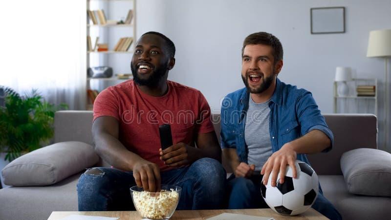 Upphetsade vänner som jublar på segern, hållande ögonen på fotbollsmatch med landslaget royaltyfri bild
