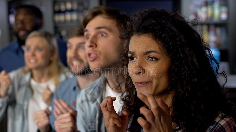 Upphetsade vänner som korsar fingrar som håller ögonen på tvkonkurrens, fans på sporthändelsen royaltyfria bilder