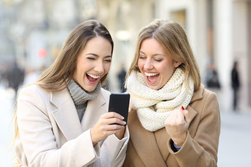 Upphetsade vänner som läser telefoninnehållet i vinter royaltyfria bilder