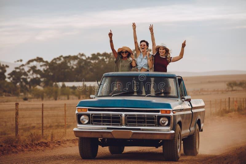 Upphetsade vänner som reser vid en pickup royaltyfria foton