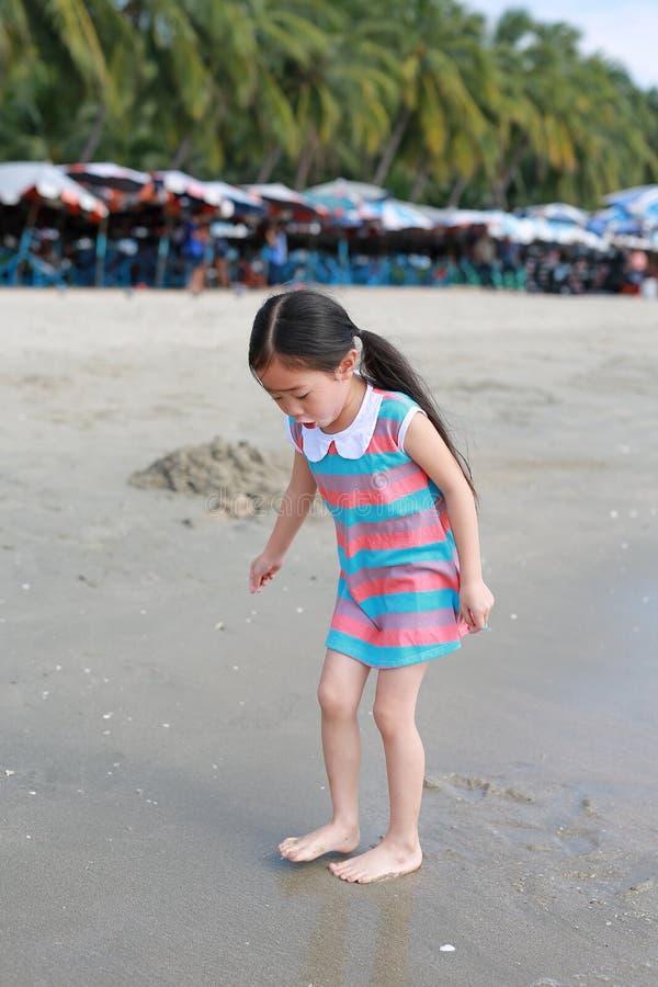 Upphetsande asiatisk barnflicka, medan kommet att spela sand och havet på stranden på ferie arkivbild
