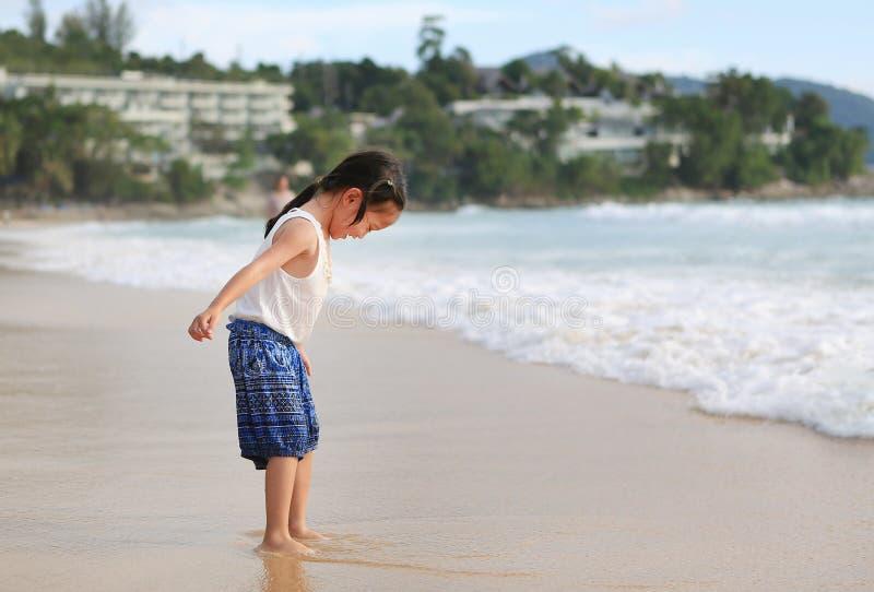 Upphetsande asiatisk barnflicka, medan kommet att spela sand och havet p? stranden p? ferie royaltyfria bilder