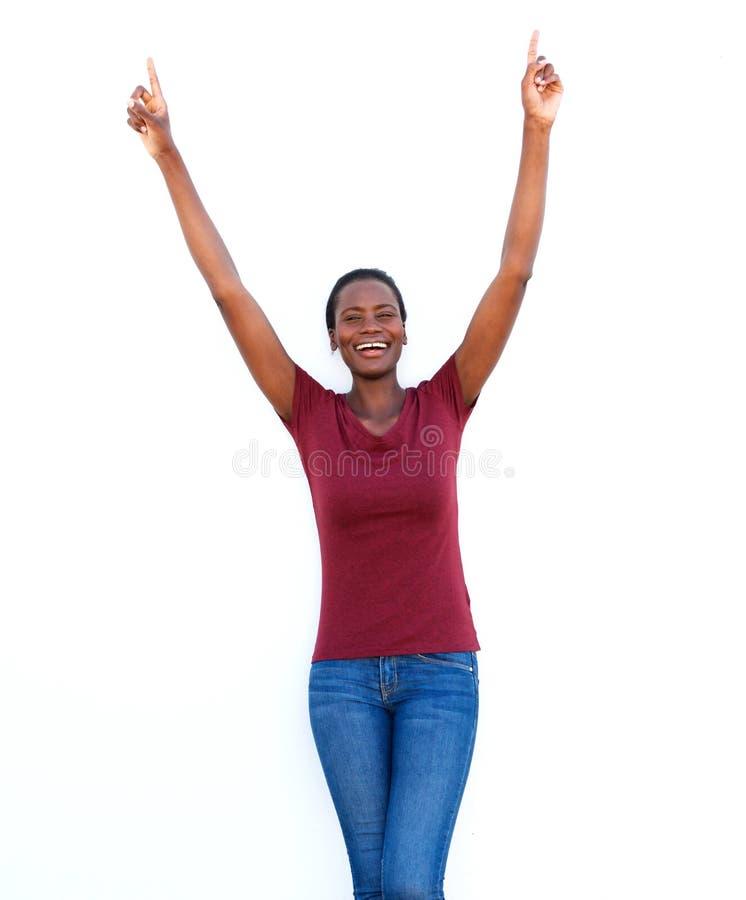 Upphetsat kvinnaanseende på vit bakgrund med hennes lyftta armar och att le arkivbild