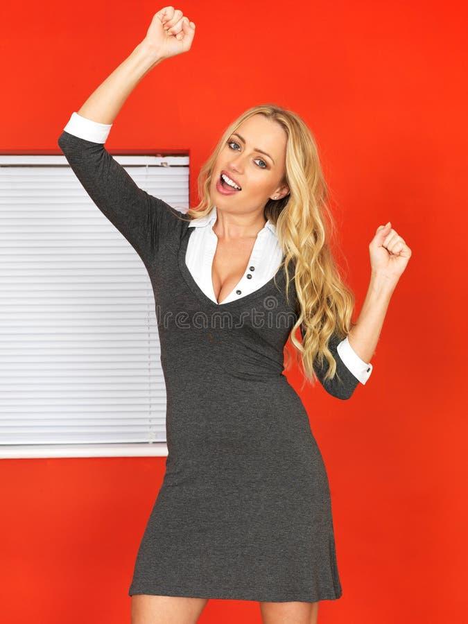 Upphetsat lyckligt ungt fira för affärskvinna royaltyfri foto