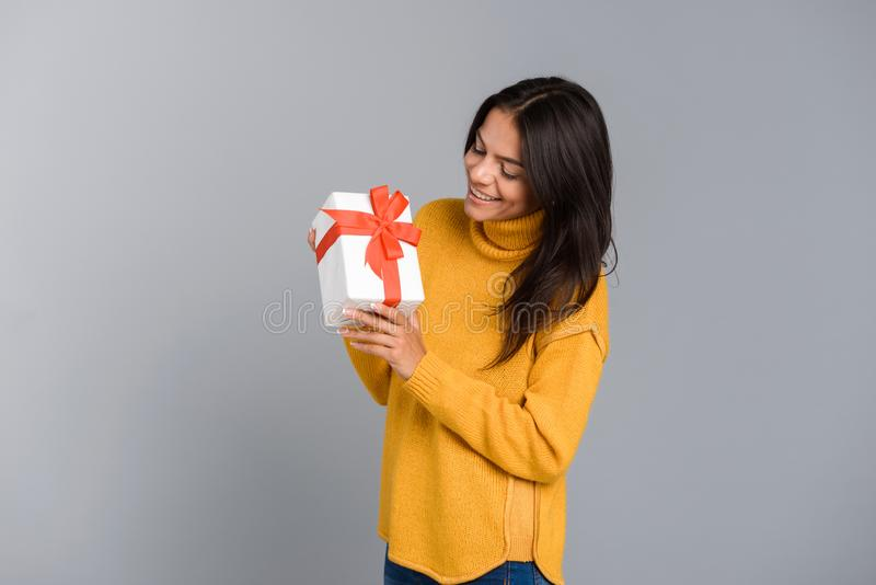 Upphetsat posera för kvinna som isoleras över grå gåva för överraskning för ask för väggbakgrundsinnehav arkivbild