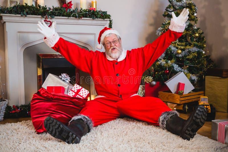 Upphetsat Santa Claus sammanträde på filten i vardagsrum royaltyfri fotografi