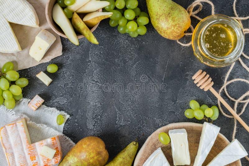 Uppläggningsfat av franska mjuka ostar från Normandie och Brittany regioner och brie som skivas med honung, päronet och gräspland arkivbild