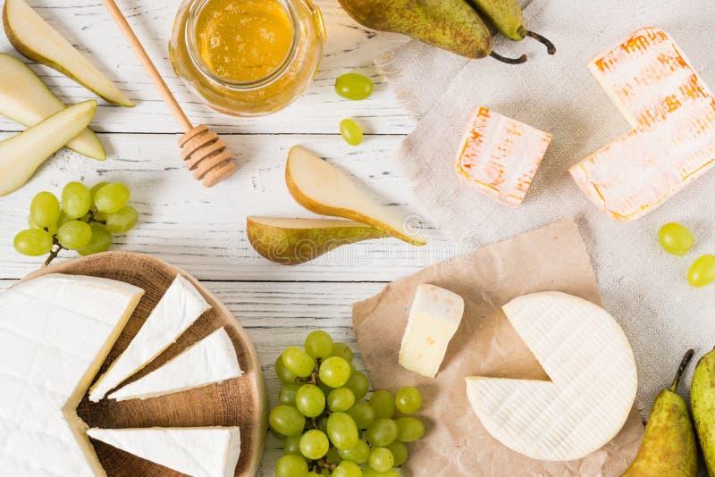 Uppläggningsfat av franska mjuka ostar som skivas med honung, päronet och gräsplandruvor fotografering för bildbyråer