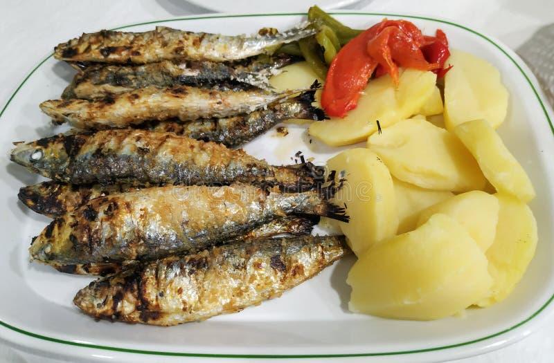Uppläggningsfat av nya grillade sardiner med potatisar och peppar Typisk maträtt i Portugal royaltyfria foton