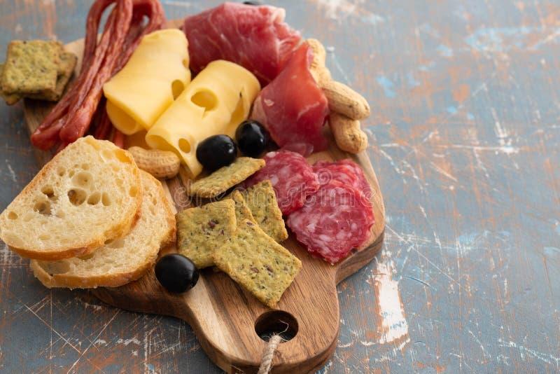 Uppläggningsfat med den spanska skinkajamon- eller italienareprosciuttocrudoen, skivad italiensk hårdost hemlagad torkad köttsala arkivfoton