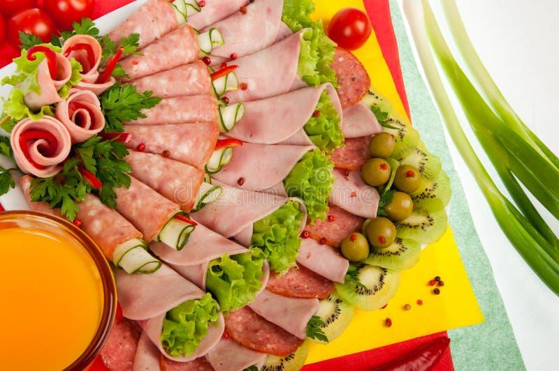 Uppläggningsfat med kallt kött som dekoreras med grönsallat arkivfoto