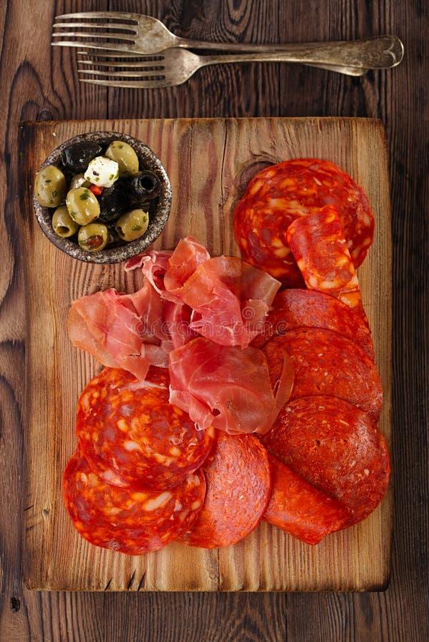 Uppläggningsfatet av serranojamon kurerade kött, chorizoen och oliv royaltyfri fotografi