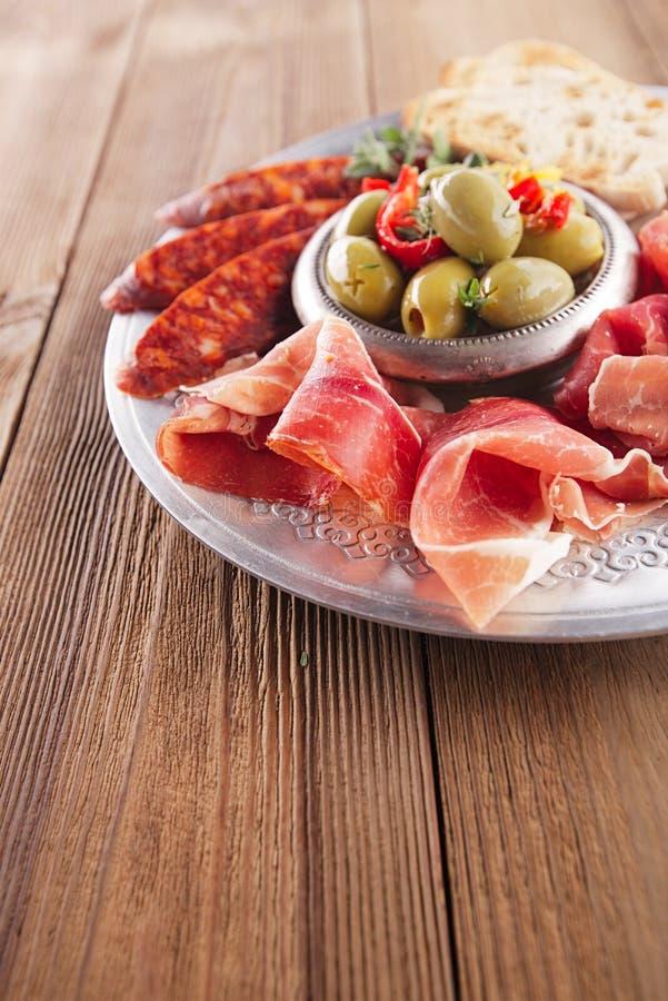 Uppläggningsfatet av serranojamon kurerade kött, Ciabatta, chorizoen och oliv arkivbild