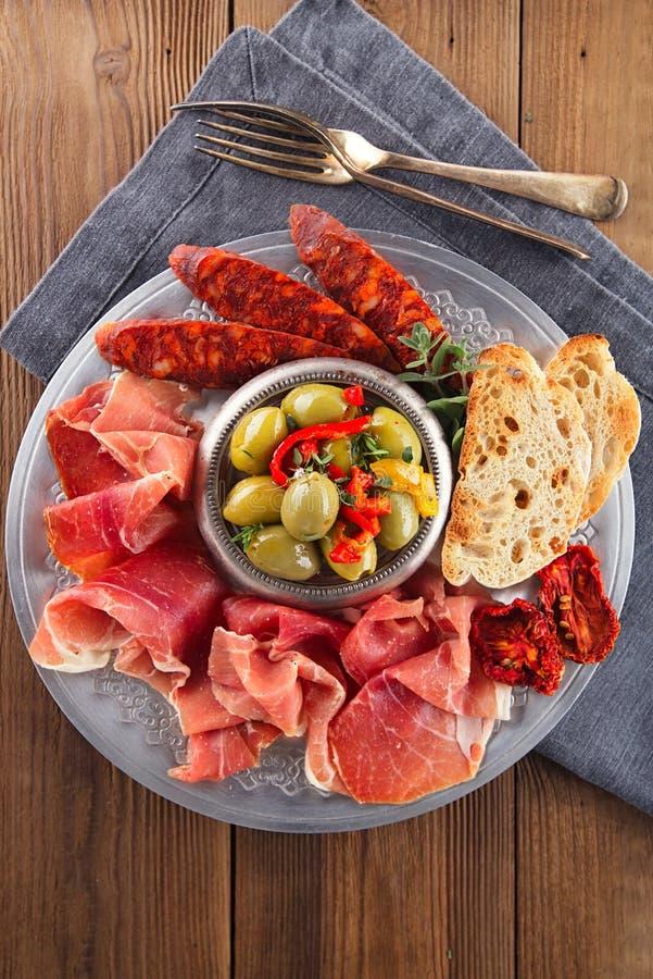 Uppläggningsfatet av serranojamon kurerade kött, Ciabatta, chorizoen och oliv arkivbilder