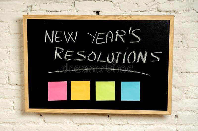 Upplösningar för nytt år som är skriftliga med krita på svart tavla med den tomma färgrika stolpen dess minneslistaanmärkningar arkivbild