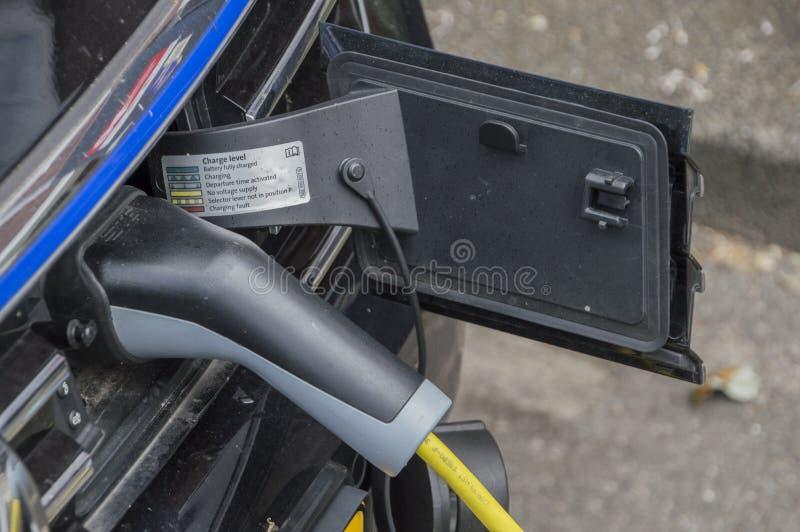 Uppladdning av en elbil på Amsterdam Nederländerna 2018 royaltyfria foton