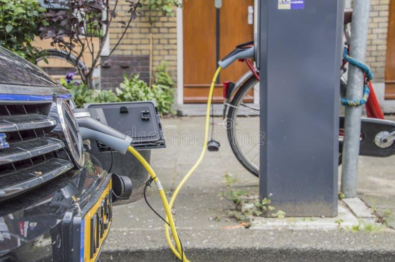 Uppladdning av en elbil på Amsterdam Nederländerna 2018 fotografering för bildbyråer
