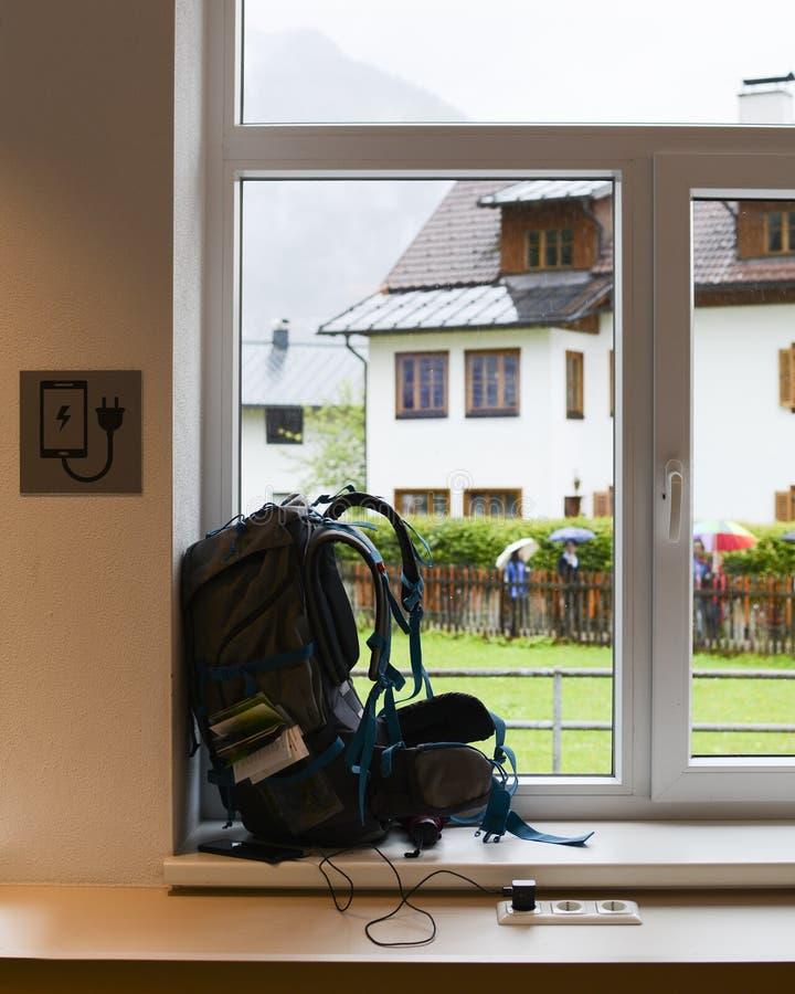 Uppladdning av telefonen En ryggsäck nära fönstret royaltyfria bilder