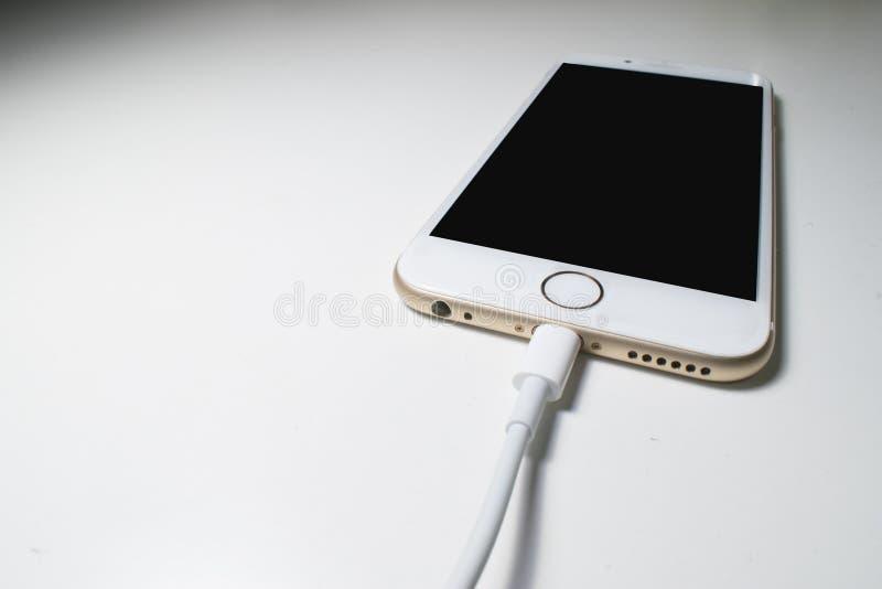 Uppladdning av telefonen, vit telefon royaltyfria bilder