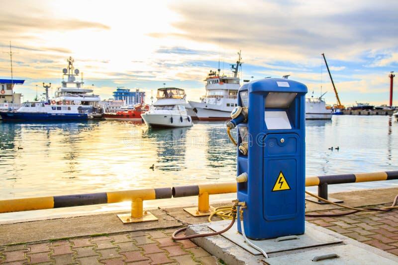 Uppladdningsstation för fartyg, elektriska uttag som laddar skepp i hamn Lyxyachter som anslutas i port på solnedgången royaltyfri bild